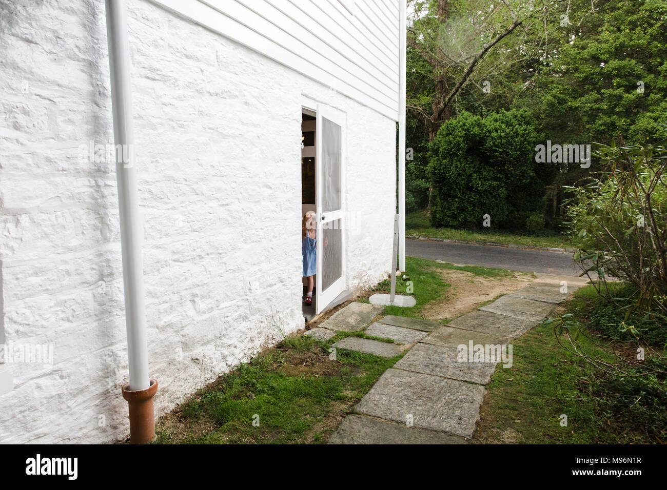 Girl halfway through side door - Stock Image