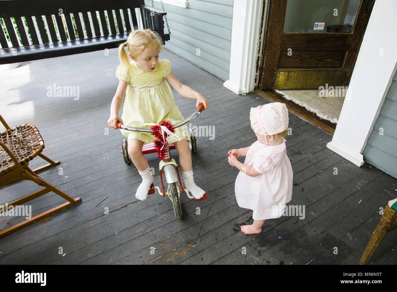 Girl riding red bike next to baby on porch - Stock Image