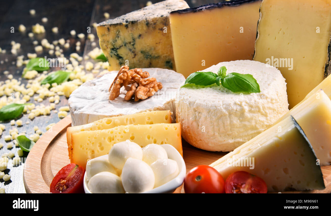 Different sorts of cheese on kitchen table. - Stock Image