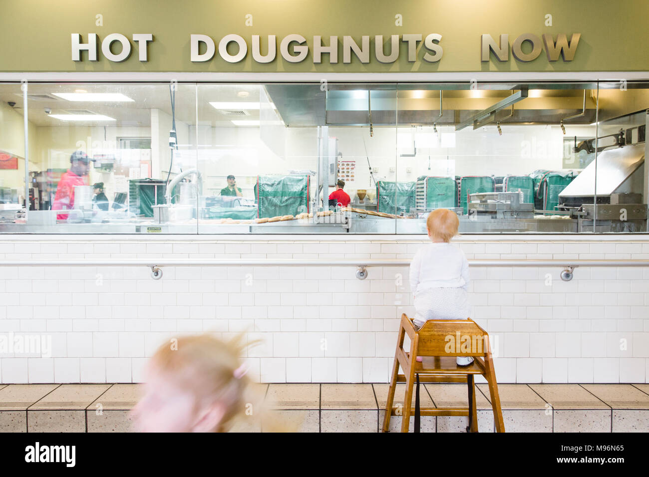 Children looking at doughnuts being prepared - Stock Image