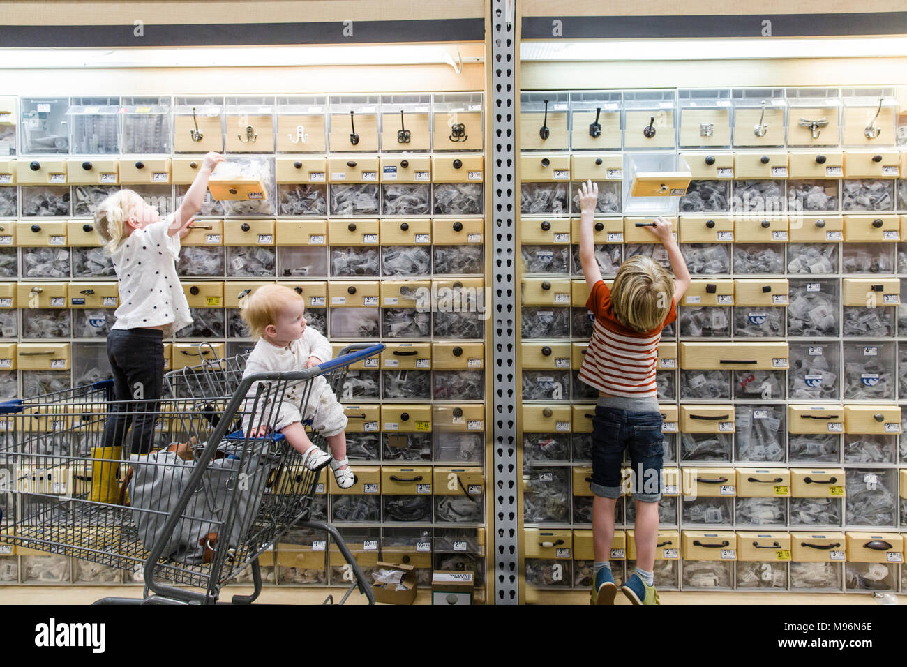 Children reaching high for boxes - Stock Image