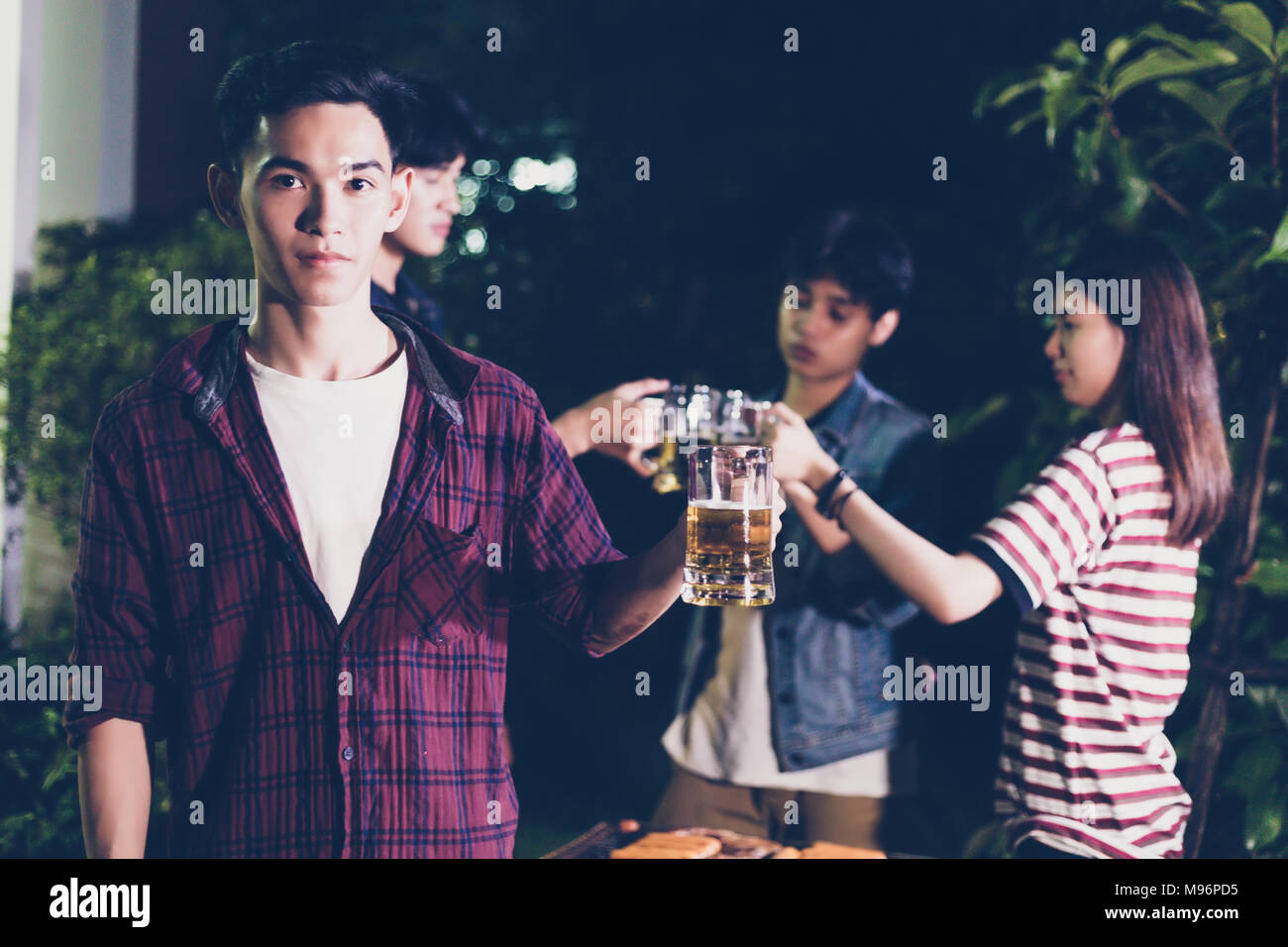 Asian group of friends having outdoor garden barbecue laughing with alcoholic beer drinks on night Stock Photo