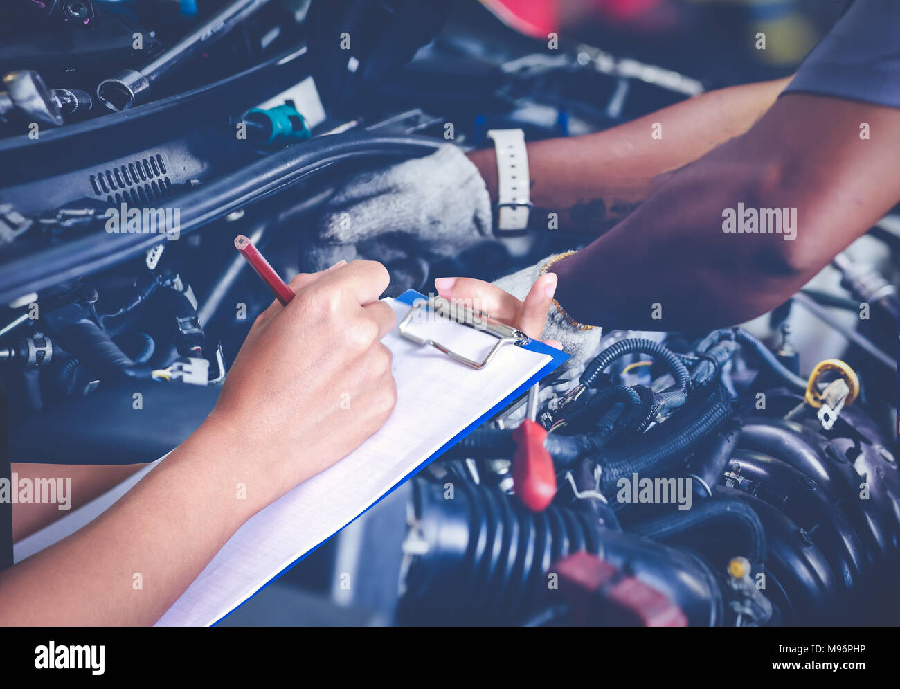 Asian women engineers and technicians are checking mechanic and inspecting on a car in auto repair shop the list on the board - Stock Image