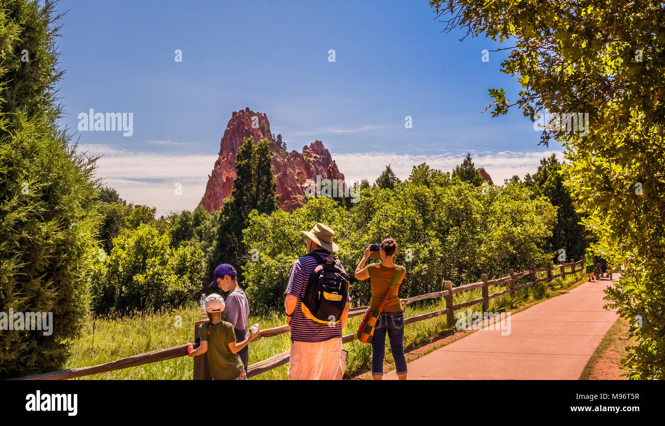 Woman and her son climbing red rocks in the Garden of the Gods park, Colorado Springs, Colorado - Stock Image