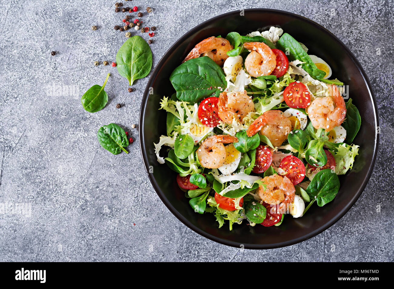 Healthy salad plate. Fresh seafood recipe. Grilled shrimps and fresh vegetable salad and egg. Grilled prawns. Healthy food. Flat lay. Top view - Stock Image