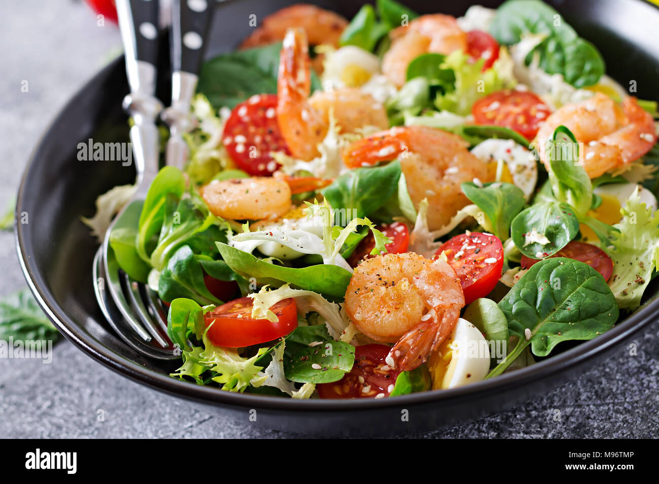 Healthy salad plate. Fresh seafood recipe. Grilled shrimps and fresh vegetable salad and egg. Grilled prawns. Healthy food. - Stock Image