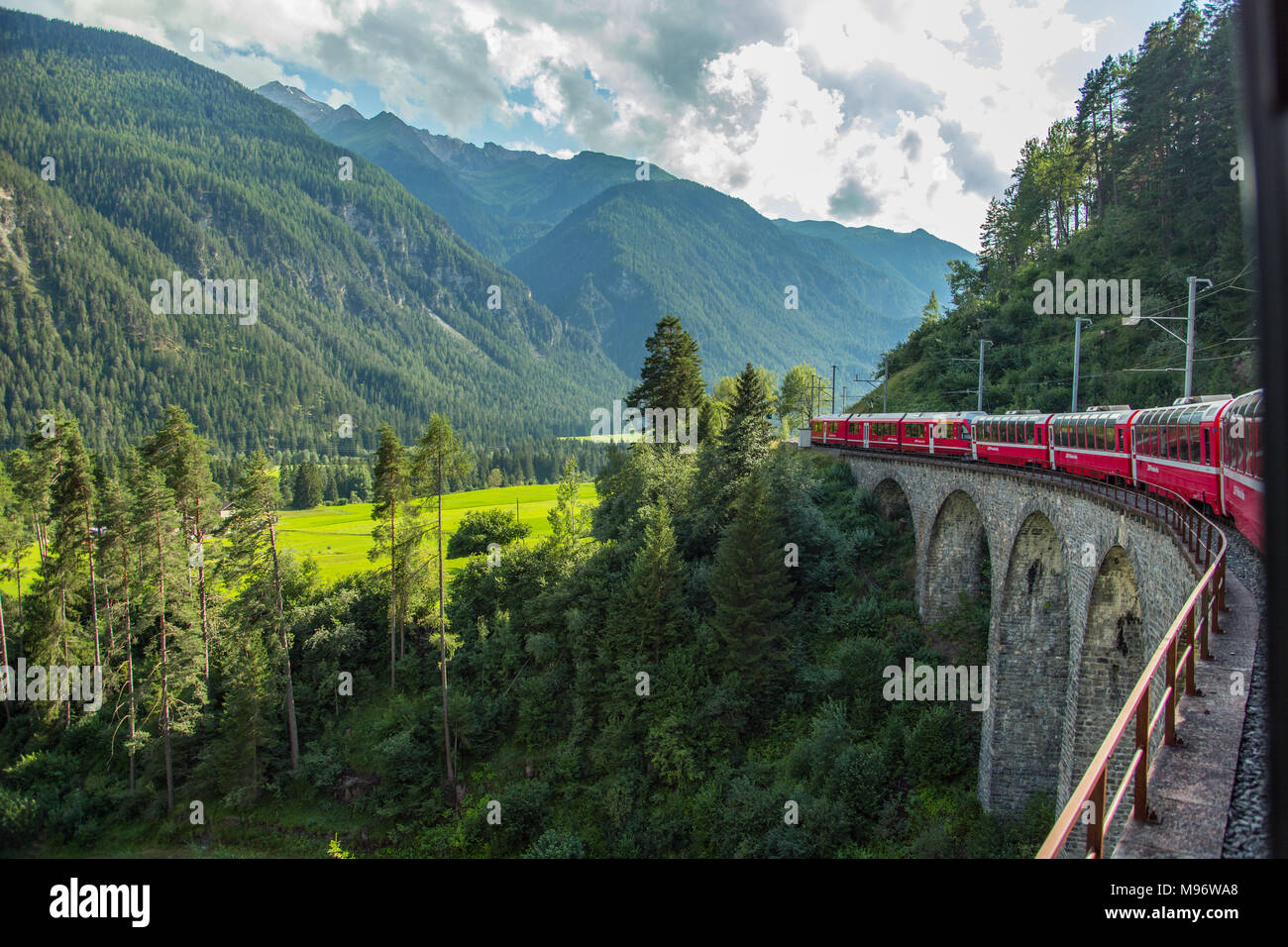 Bernina Express Train Travels Through Swiss Alps Over Viaducts - Stock Image