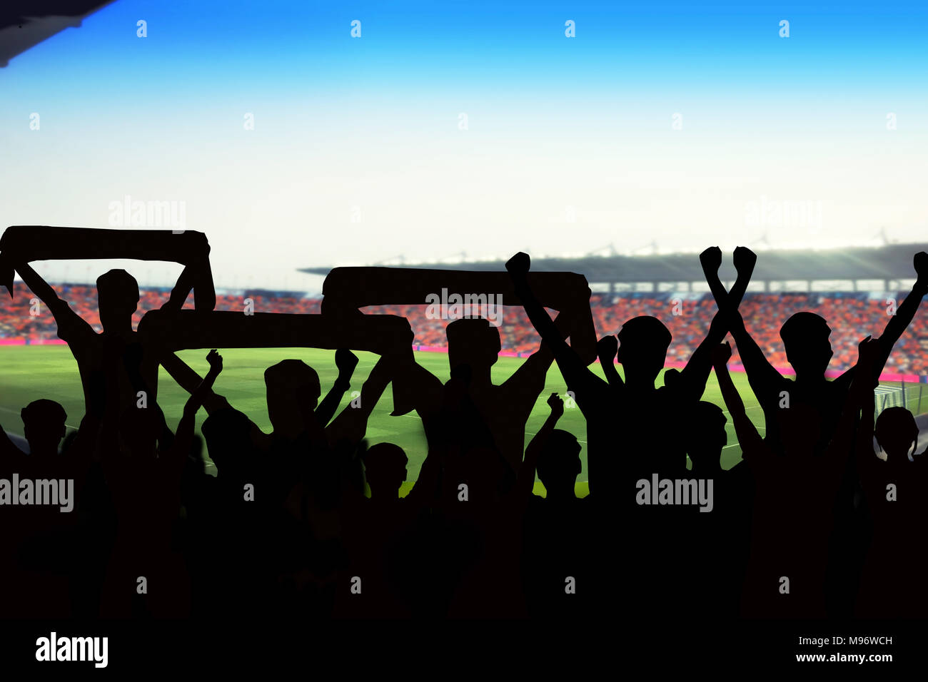 silhouettes of Soccer fans in a match and Spectators at football stadium - Stock Image