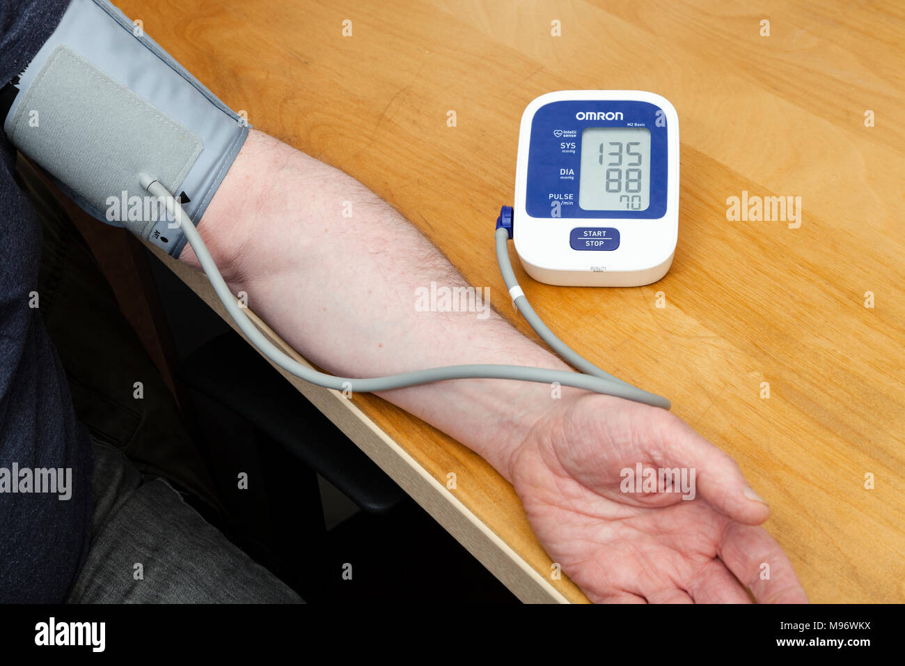 Person using an Omron blood pressure monitor attached to their arm - Stock Image