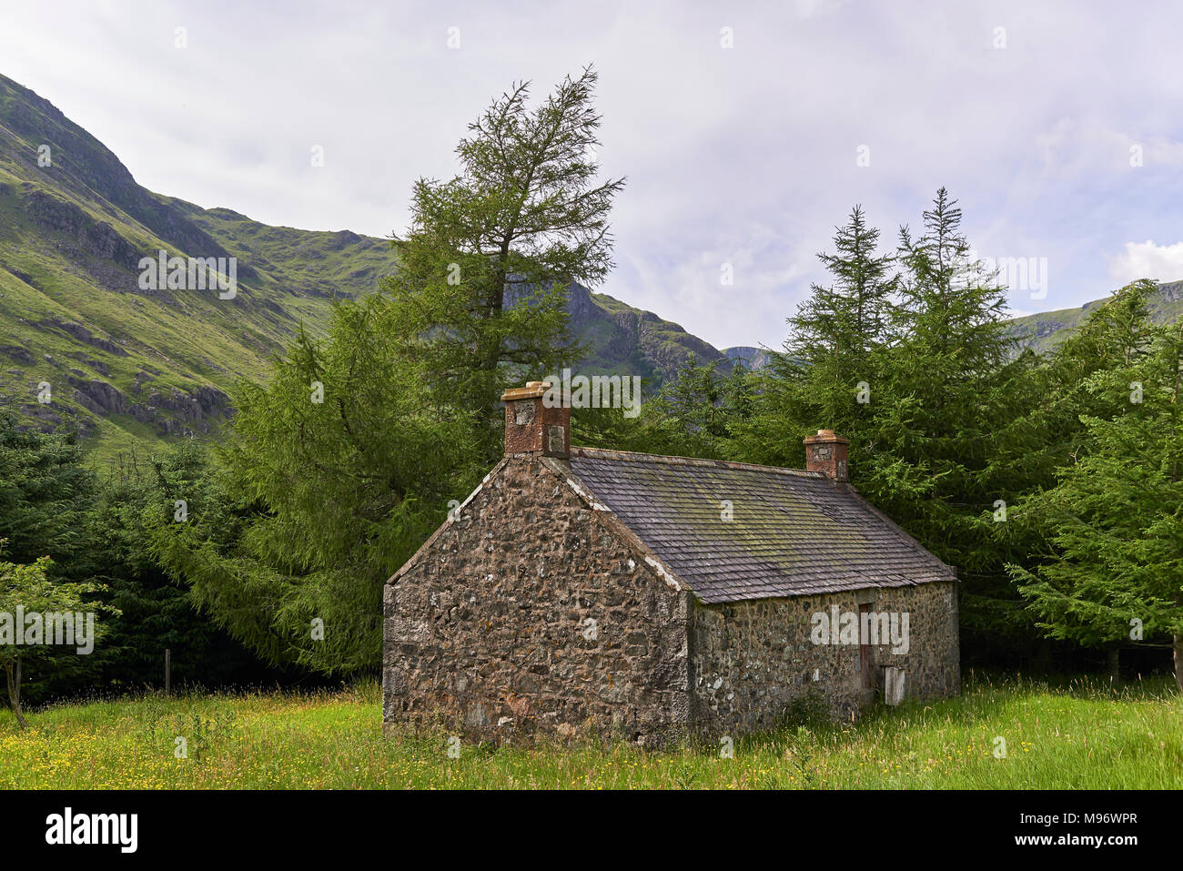 A stone built Mountain Bothy lies situated in a sheltered position within a Mountain Meadow in Glen Doll, Angus, Scotland, part of the Cairngorm Natio - Stock Image