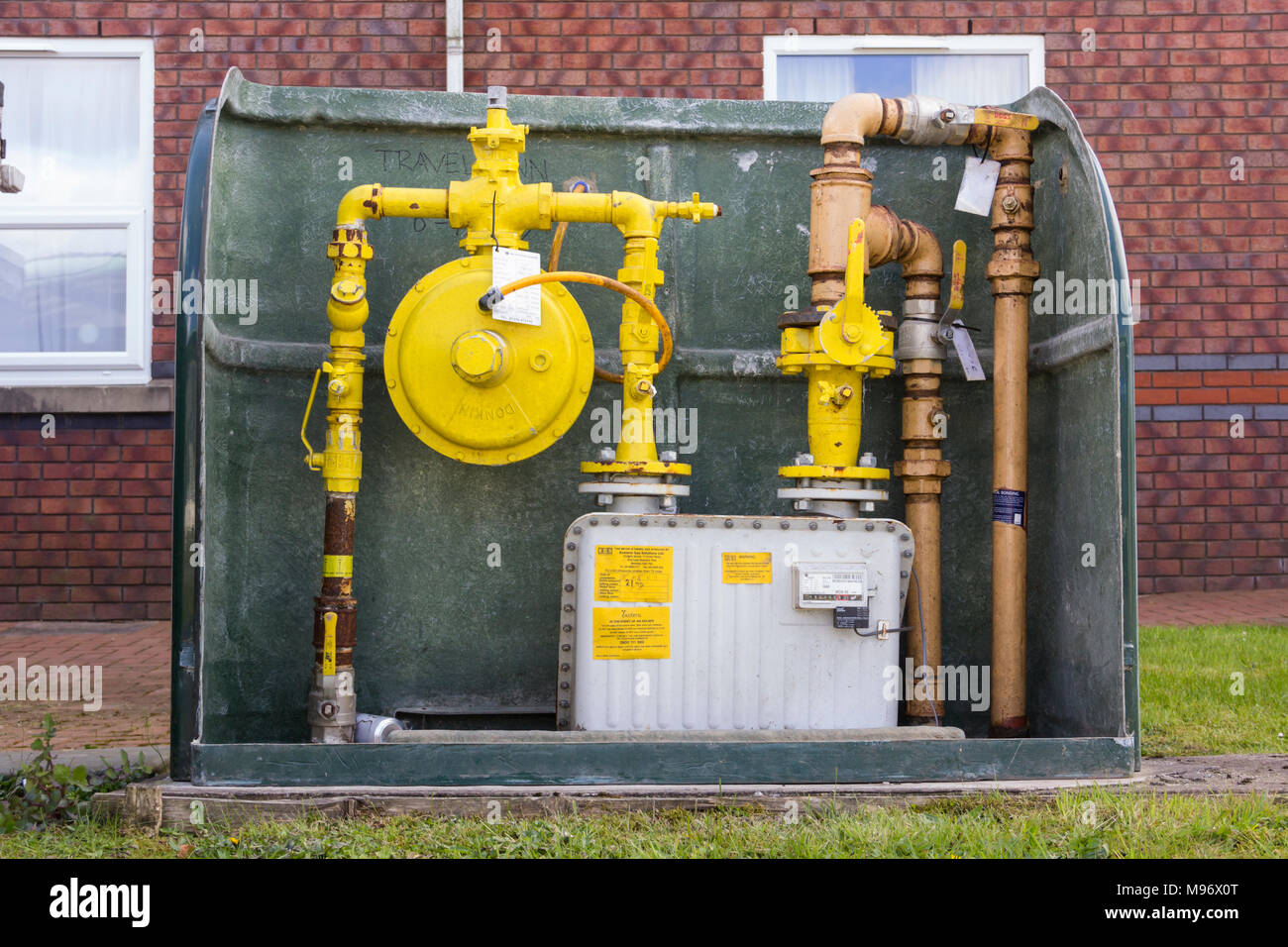 Commercial gas meter, piping and valves outside a hotel building in the UK. - Stock Image