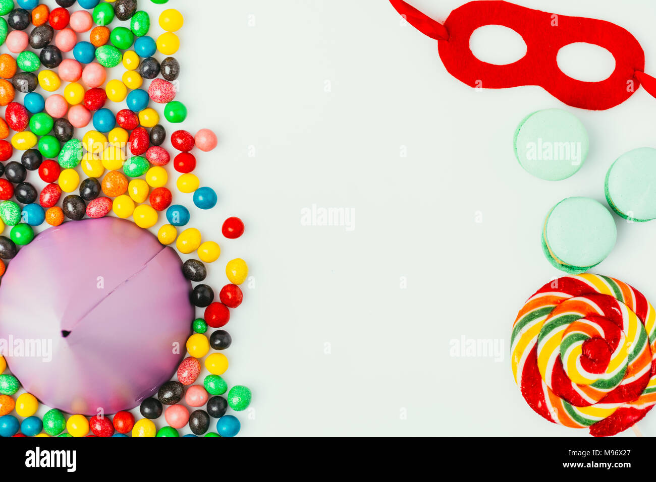 top view of arranged party cone, masquerade mask, macarons and candies isolated on grey - Stock Image