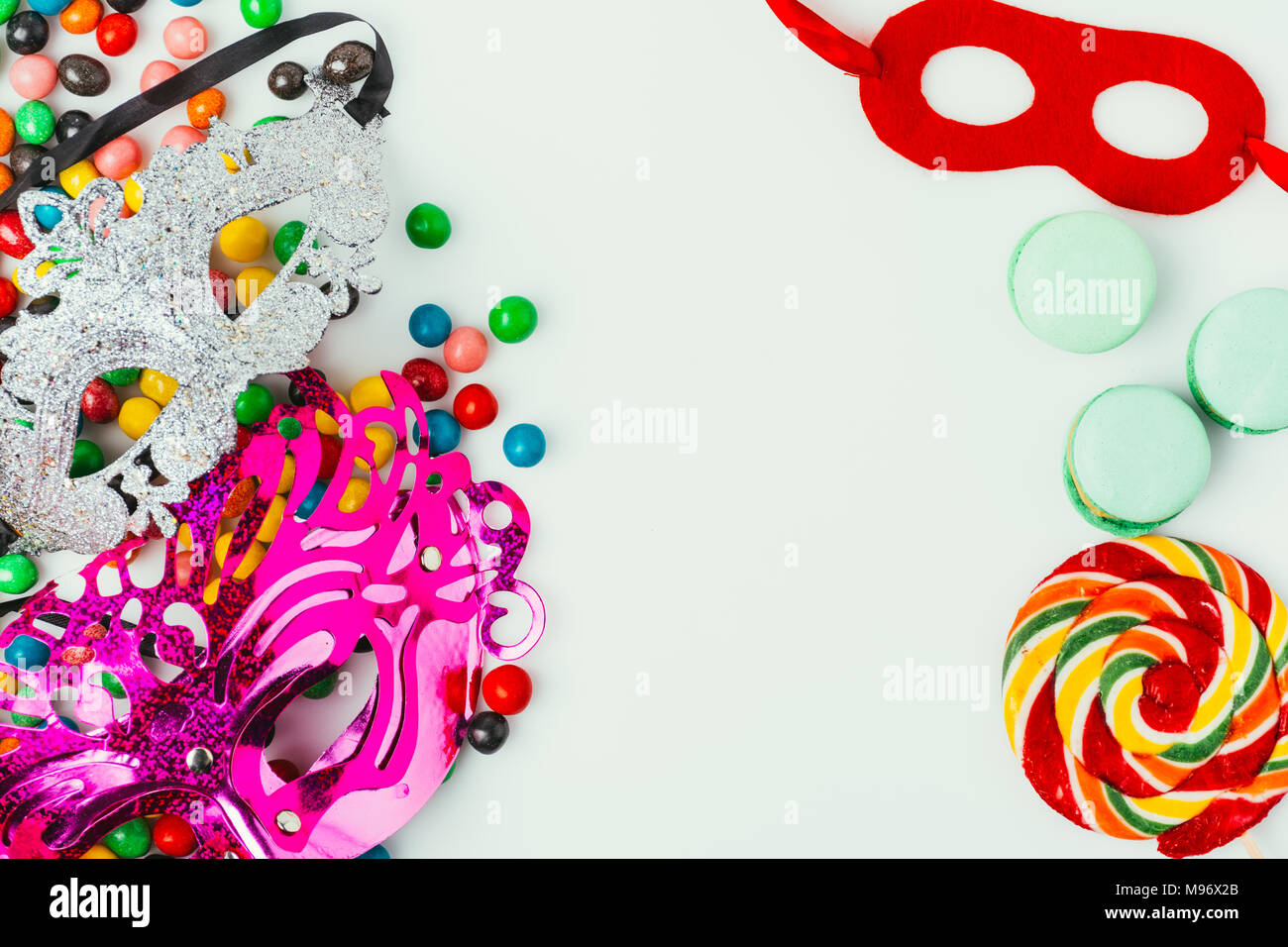 top view of arranged masquerade masks, macarons and candies isolated on grey, purim holiday concept - Stock Image