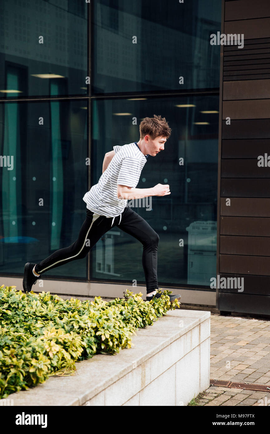 Freerunner is jumping between walls in the city. - Stock Image