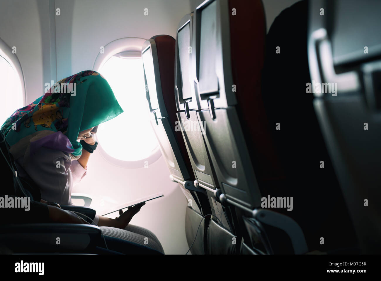 Female lonely muslim traveling on plane while reading on seats during a sunset, lowlight ambience mode - Stock Image