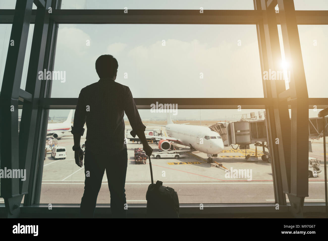 Back side of traveler boy in termainal at airport looking at the flying plane above airport, travel and vacation lifestyle concept - Stock Image