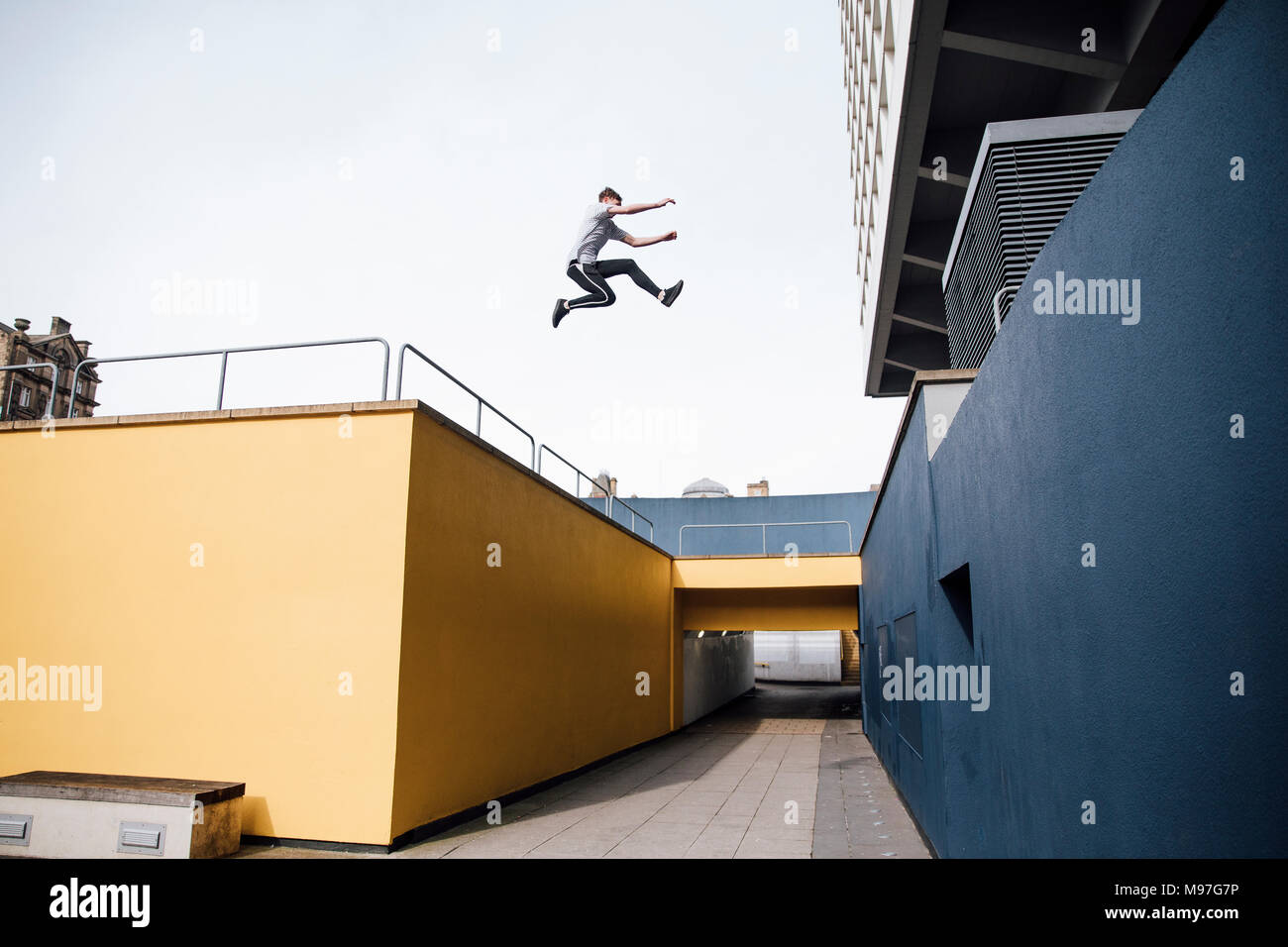 Freerunner is jumping beween colourful buildings in the city. Stock Photo