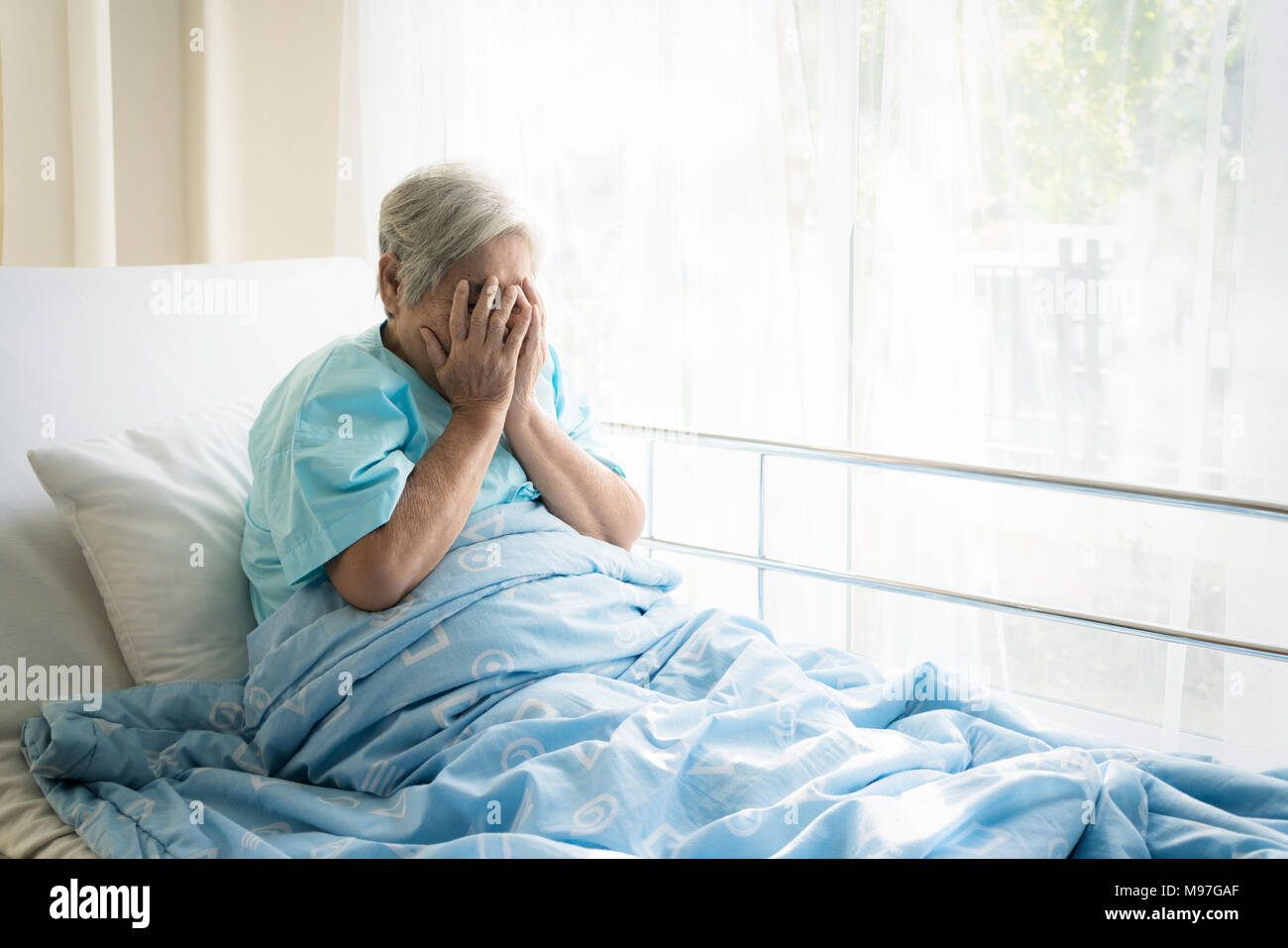 Asian depressed elderly woman patients lying on bed looking out the window in hospital. Elderly woman patients is glad recovered from the illness. - Stock Image