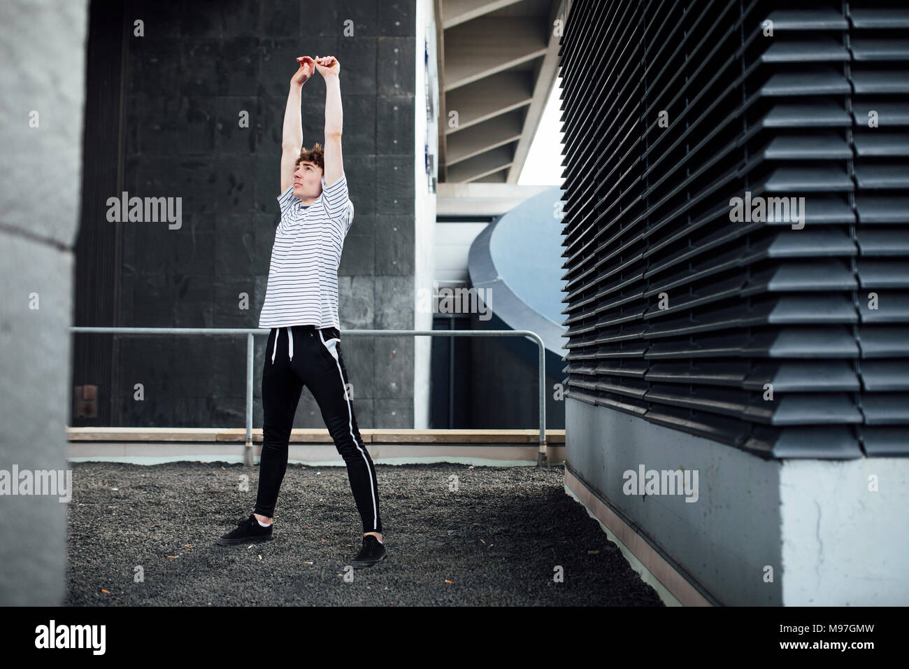 Freerunner is stretching on a rooftop. - Stock Image