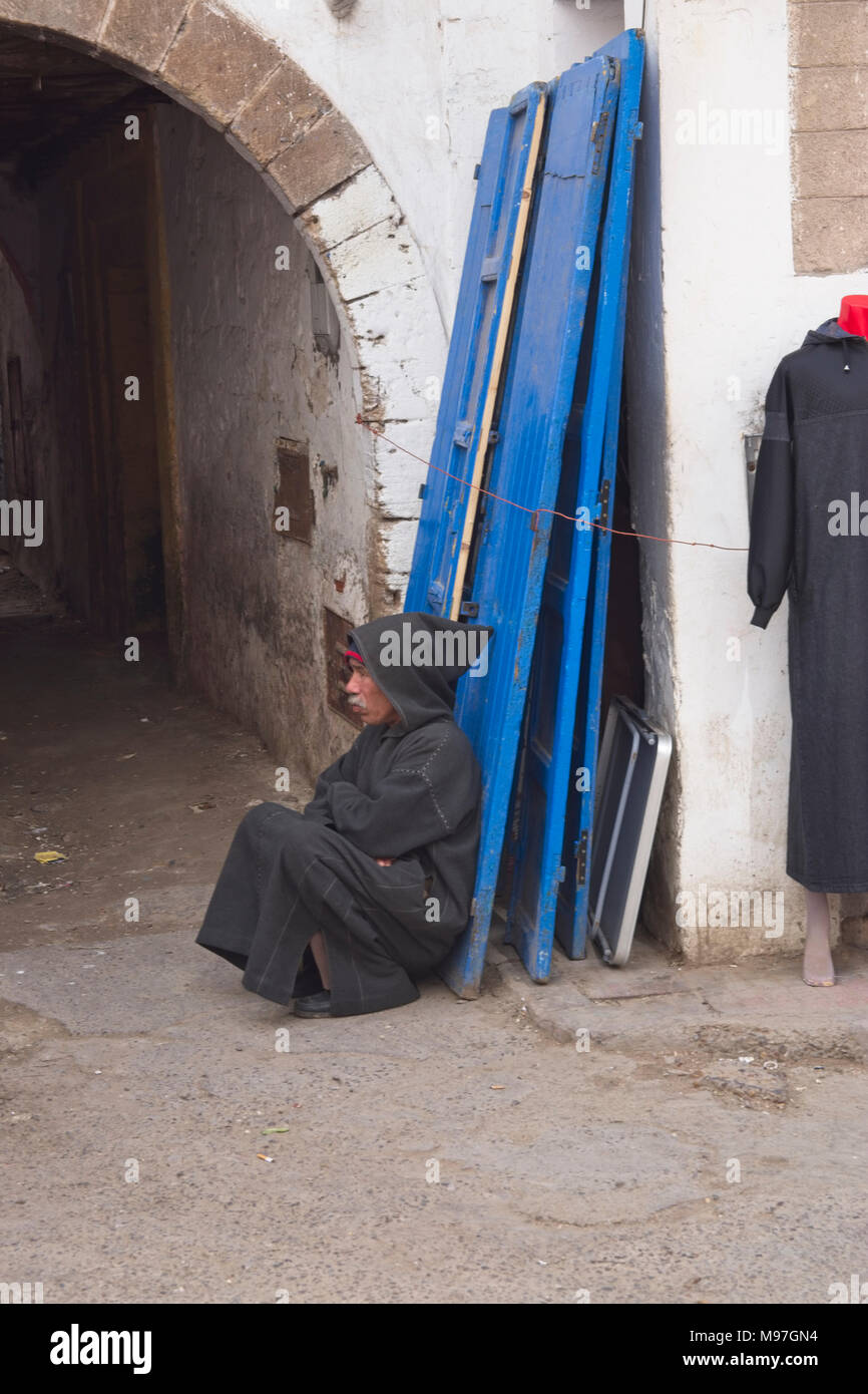 Elderly man in black Berber coat squatting at arched entrance. - Stock Image