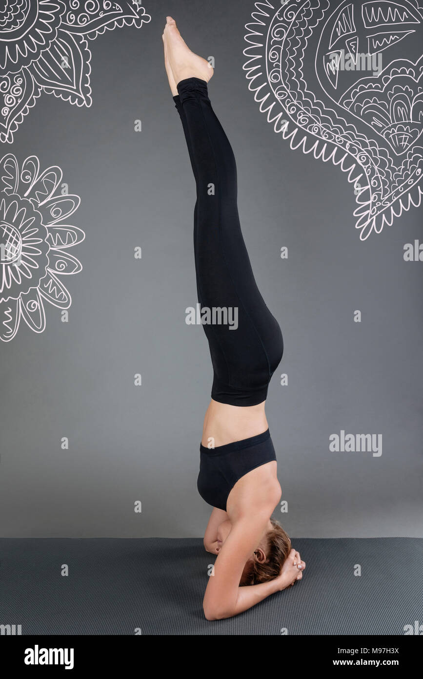Calm woman standing on her head while doing physical exercises - Stock Image