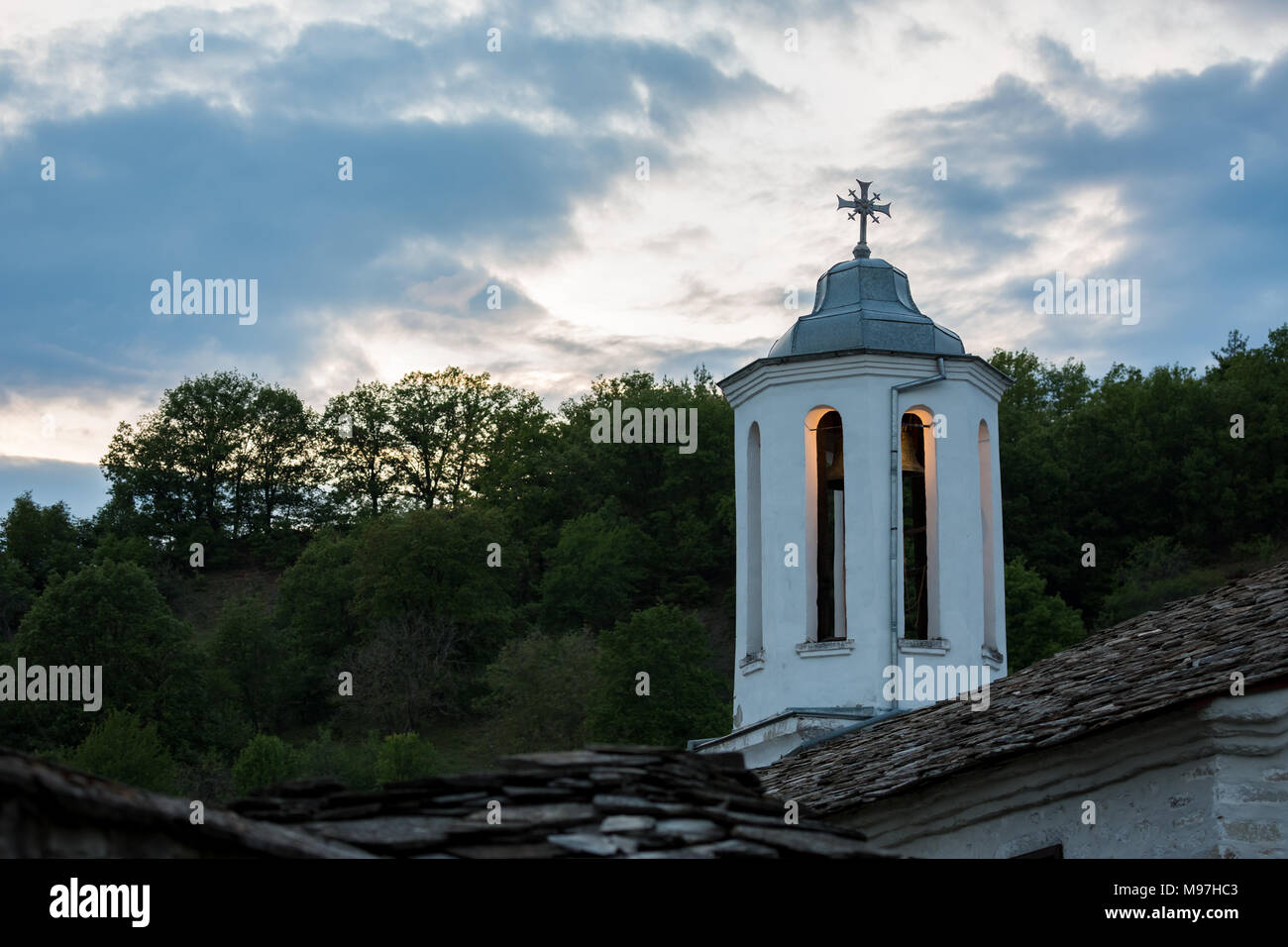 Lit dome of orthodox church with decorated cross and brass bell at evening, village of Dolen, Rhodope mountain, Bulgaria with cloudy sky background - Stock Image