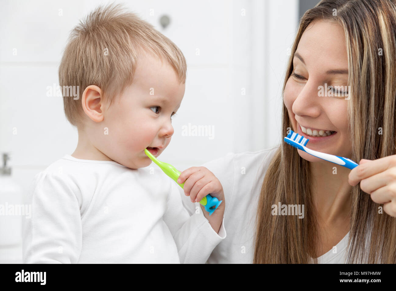 Happy mother teaching her son how to bush teeth in the bathroom - Stock Image