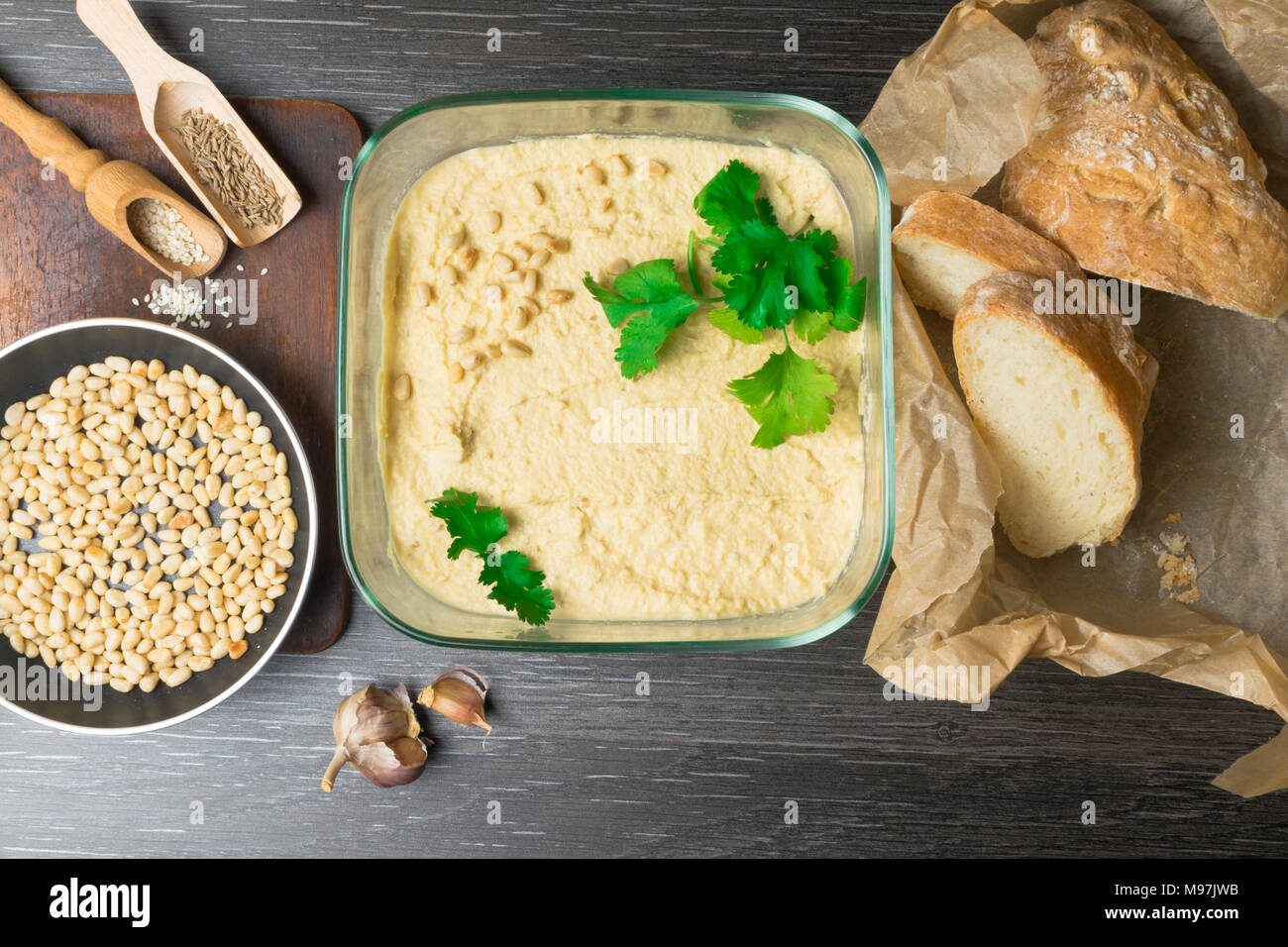 Hummus or houmous, appetizer made of mashed chickpeas with tahini, lemon, garlic, olive oil, parsley, cumin on wooden table - Stock Image