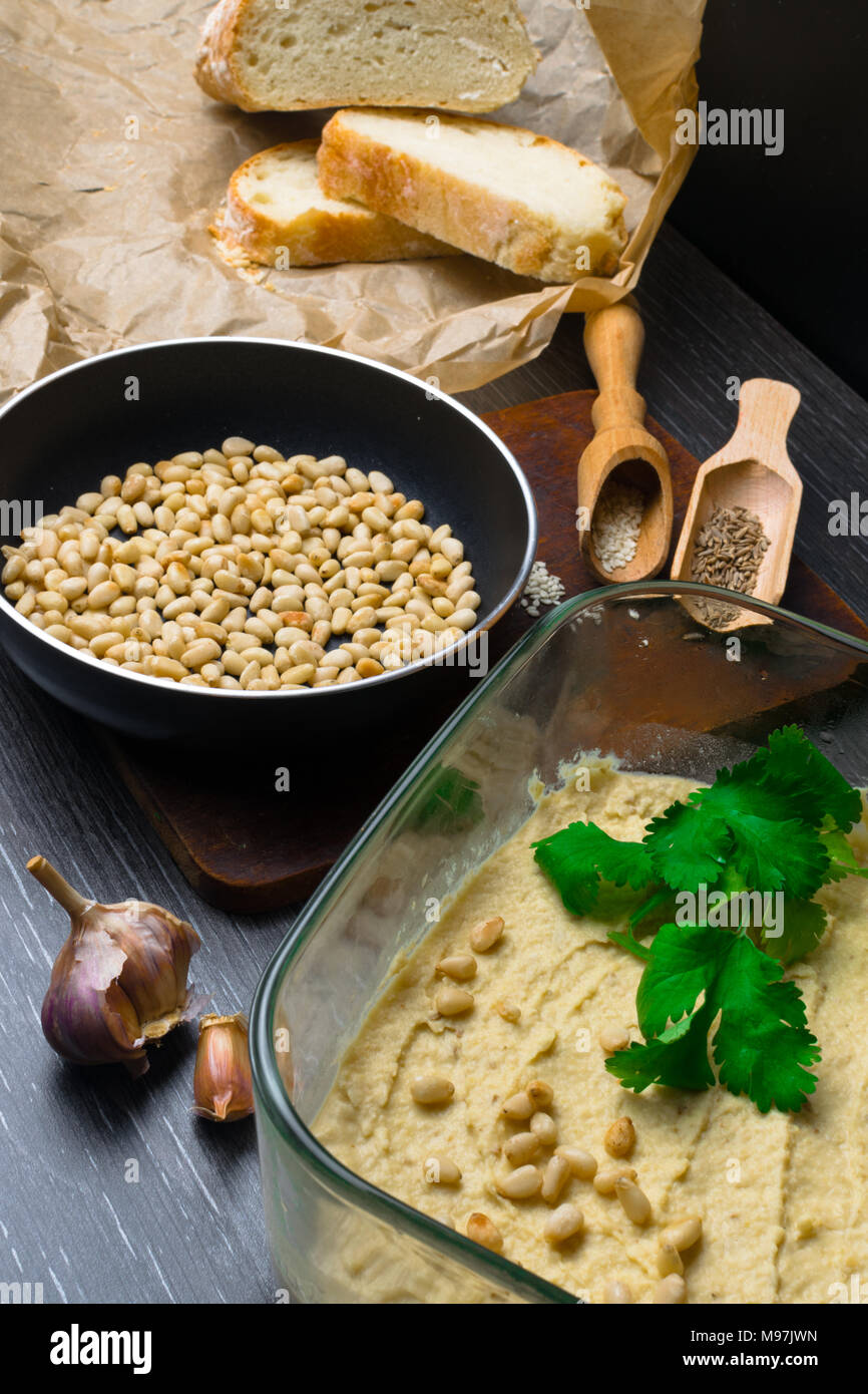 Hummus or houmous, appetizer made of mashed chickpeas with tahini, lemon, garlic, olive oil, parsley, cumin and cedar nuts on wooden table - Stock Image