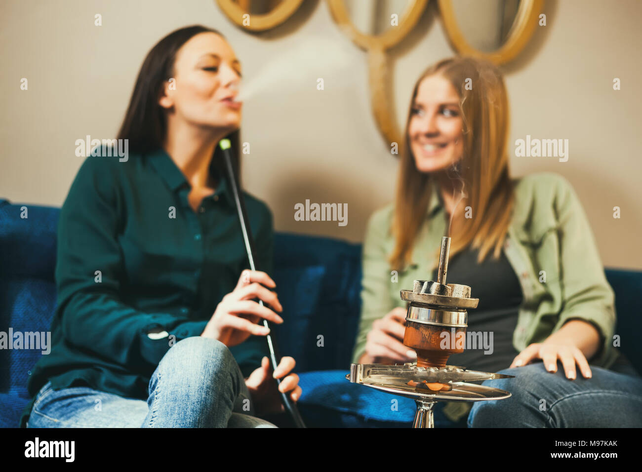 Two happy women are sitting in shisha bar and smoking nargile - Stock Image