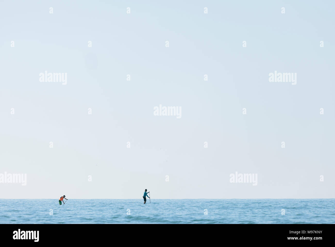 Three men on a paddle surf in the middle of the Mediterranean sea - Stock Image