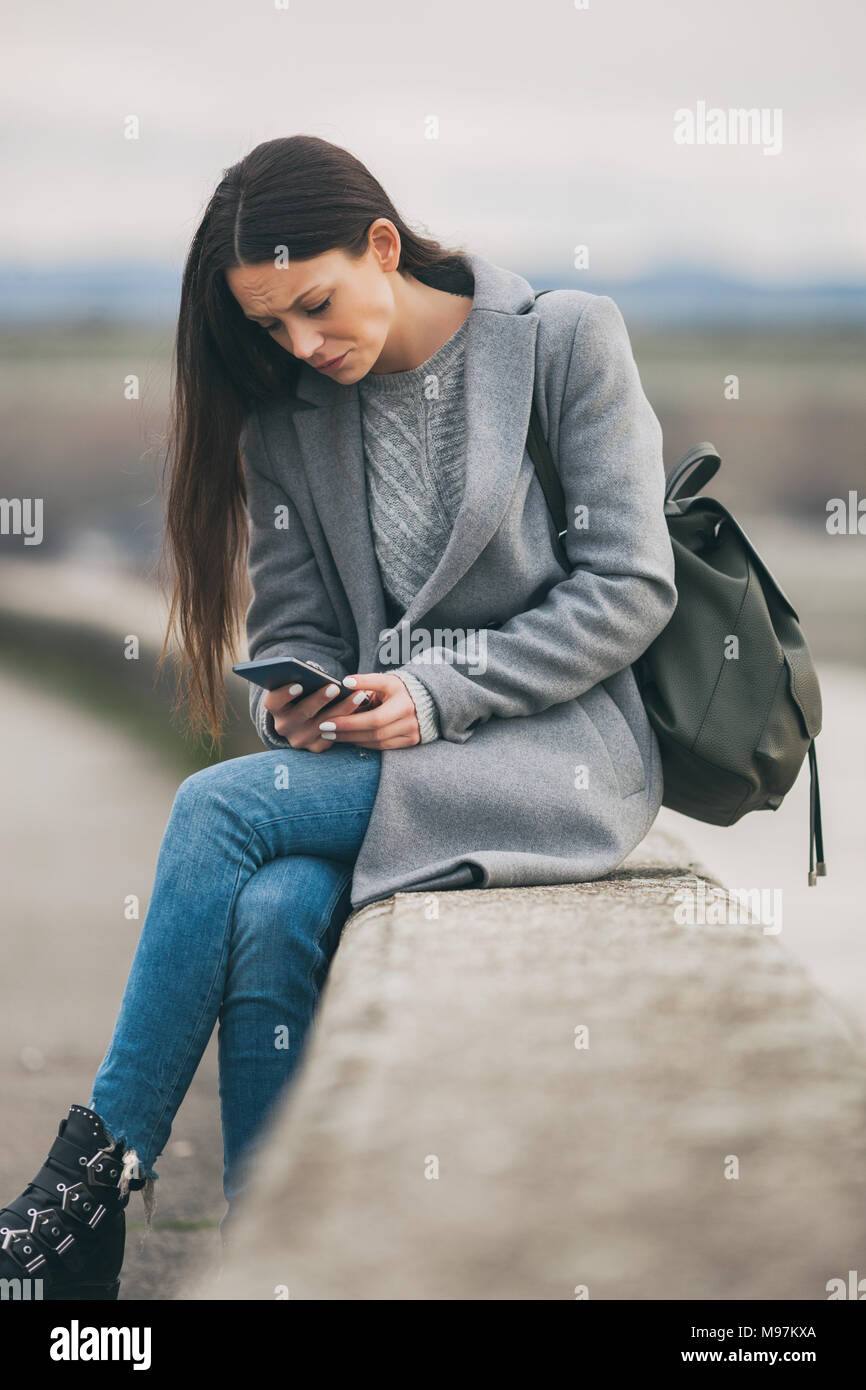 Young lonely and depressed woman is sitting in grief. - Stock Image