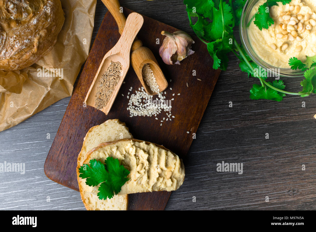 Traditional Hummus or houmous, appetizer made of mashed chickpeas with tahini, lemon, garlic, olive oil, parsley, cumin and cedar nuts on wooden table. Healthy lifestyle and eating right concept - Stock Image