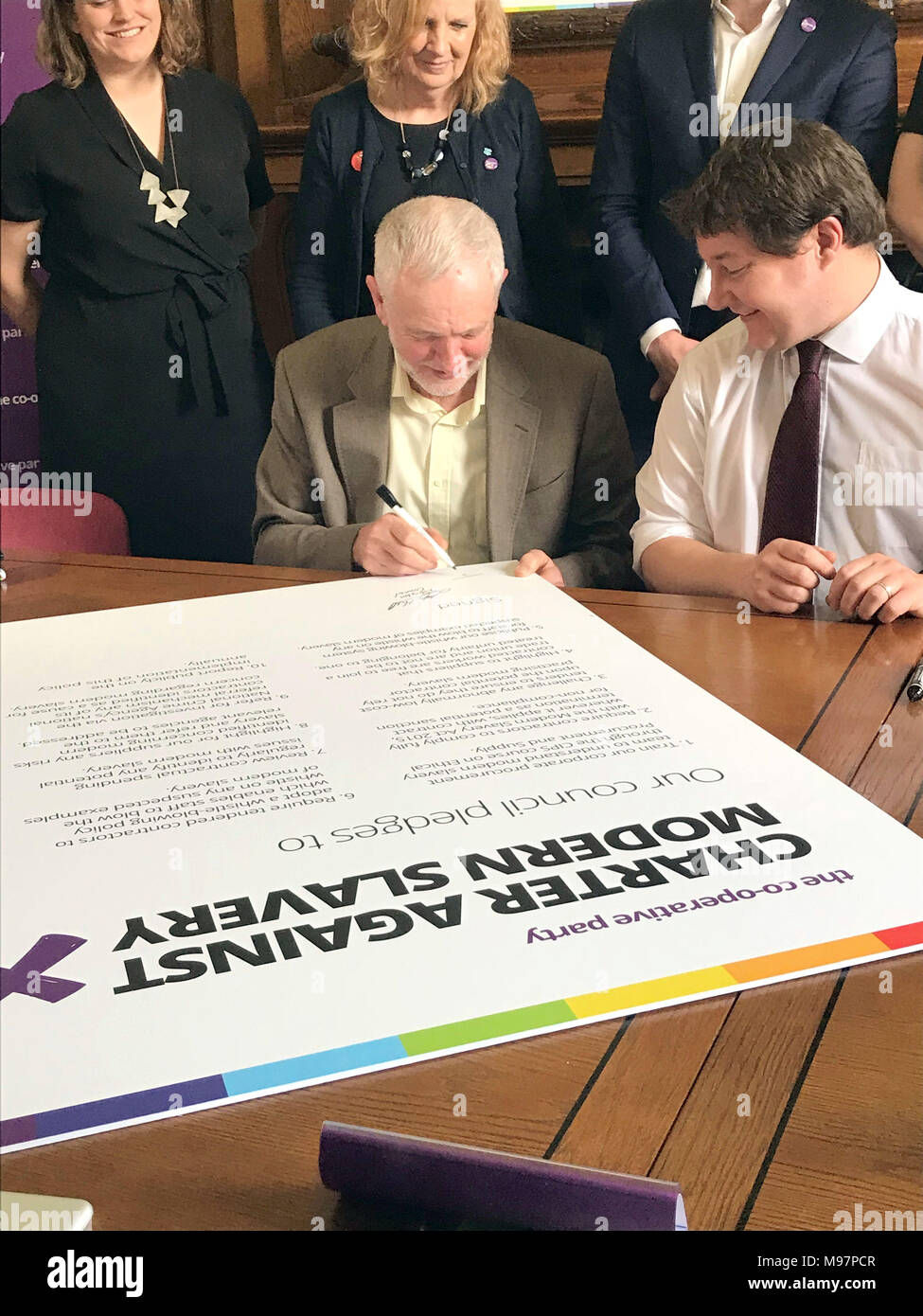 Jeremy Corbyn signs a local government pledge against modern slavery, as he calls on every council in the UK to sign a local government charter against the practice at Islington town hall on Friday afternoon. - Stock Image