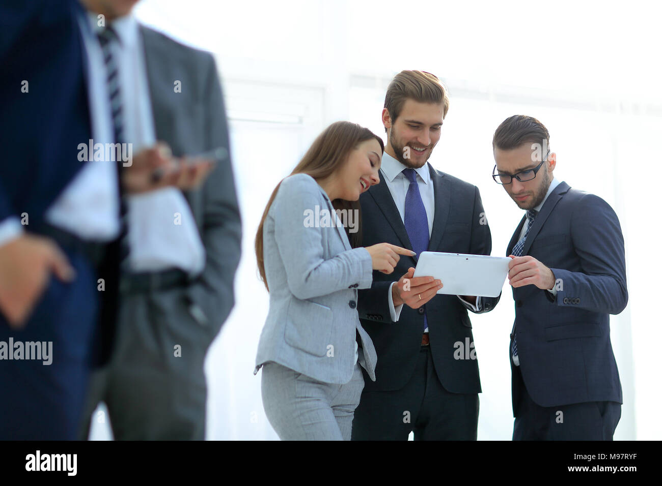 Business people are using gadgets and smiling while working - Stock Image