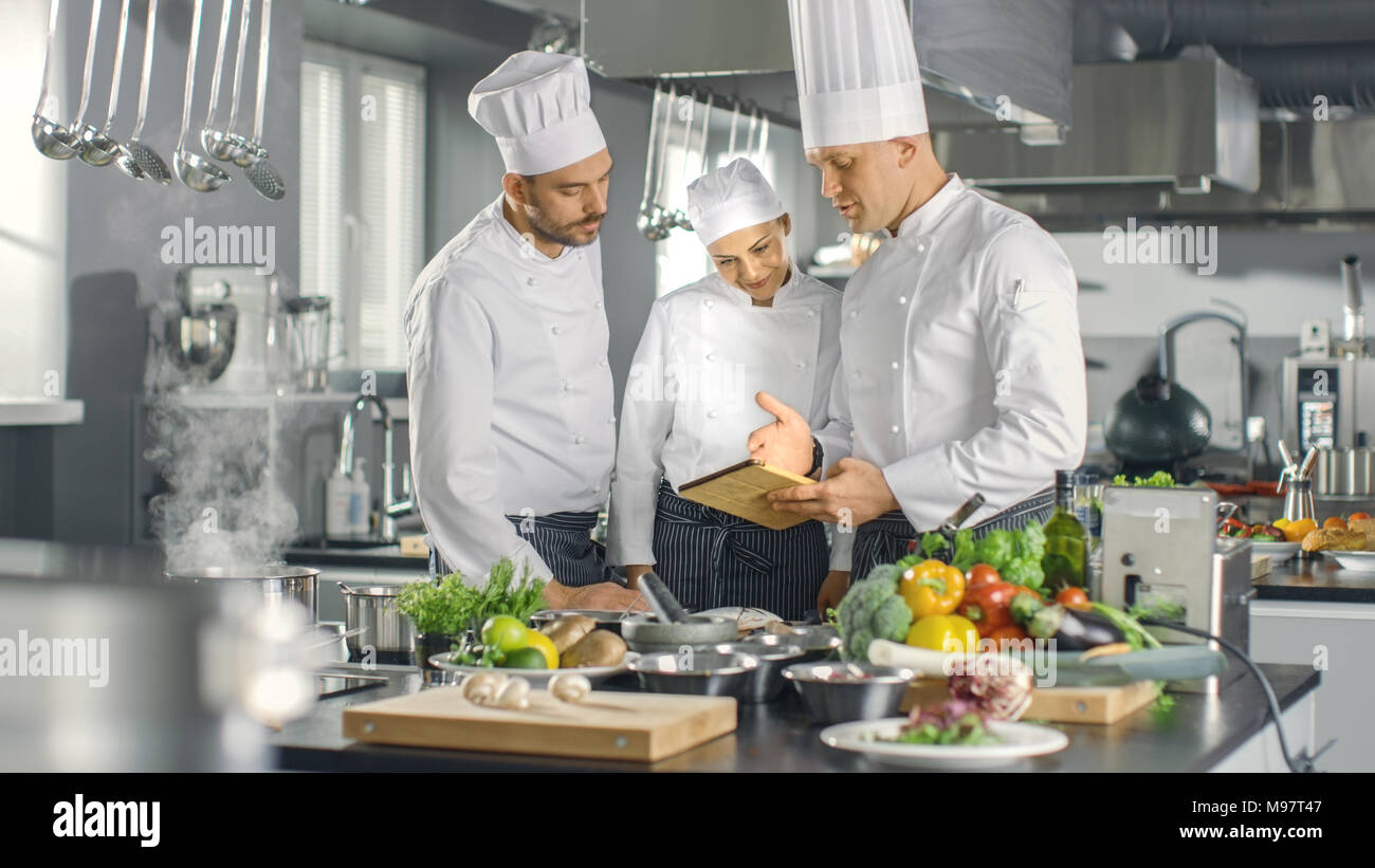 In The Modern Kitchen Team Of Cooks Use Tablet Computer For