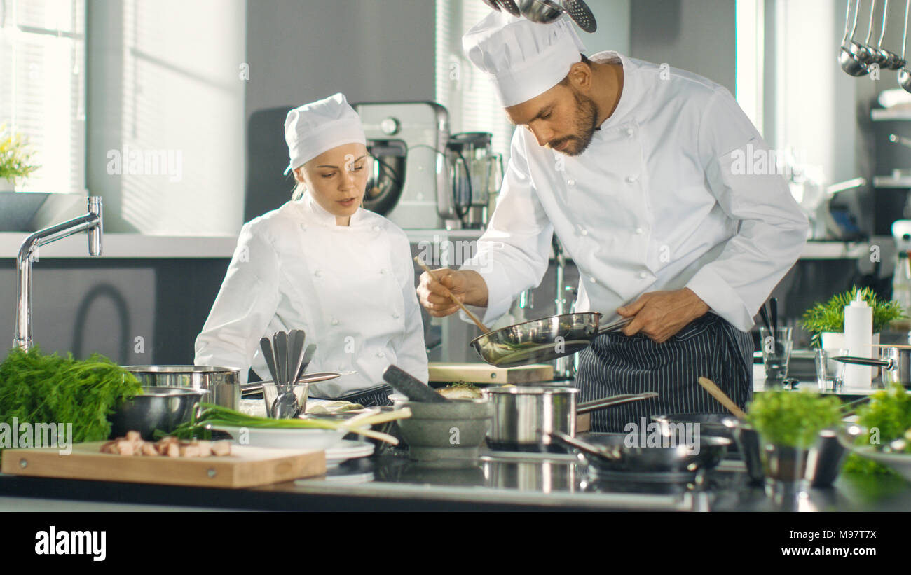 Famous Chef And His Female Apprentice Prepare Special Dish In A Modern Five Star Restaurant S Kitchen Stock Photo Alamy