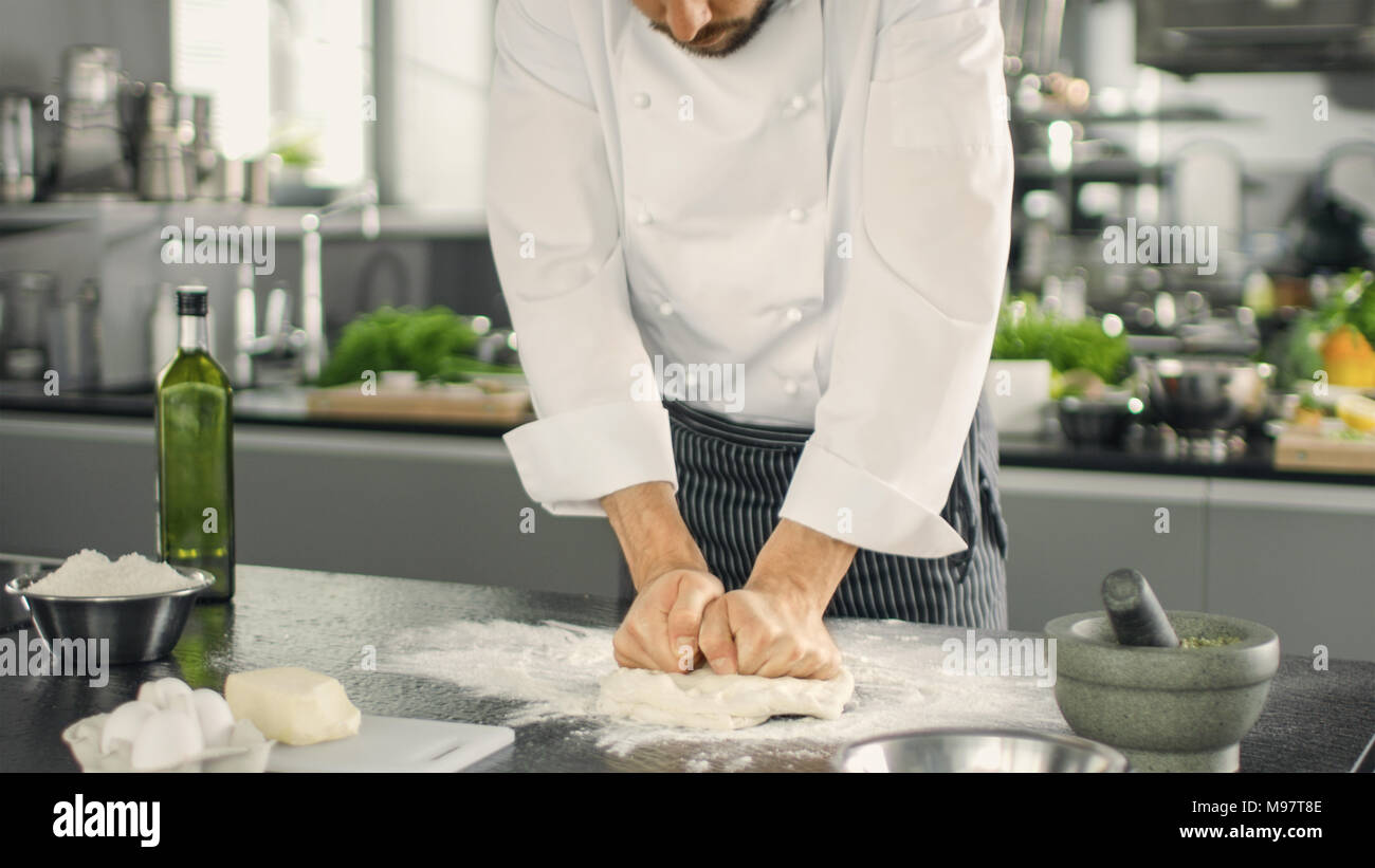 Baker Chef of Famous Restaurant Kneads the Dough in a Modern Looking Kitchen. - Stock Image