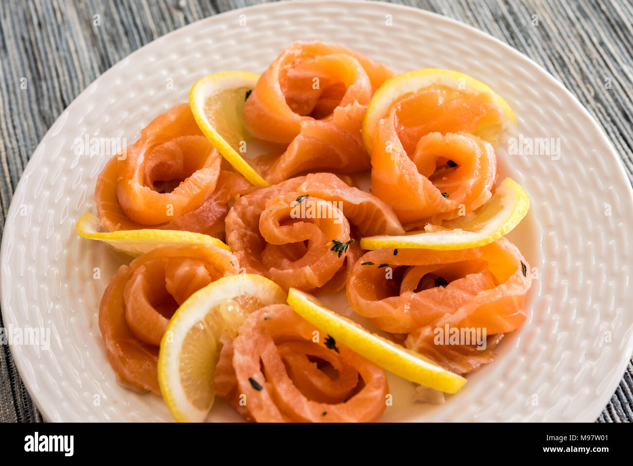 b930bb31c63e Fresh Raw Salmon fillet swirls on a white plate with lemon olive oil and  thyme -