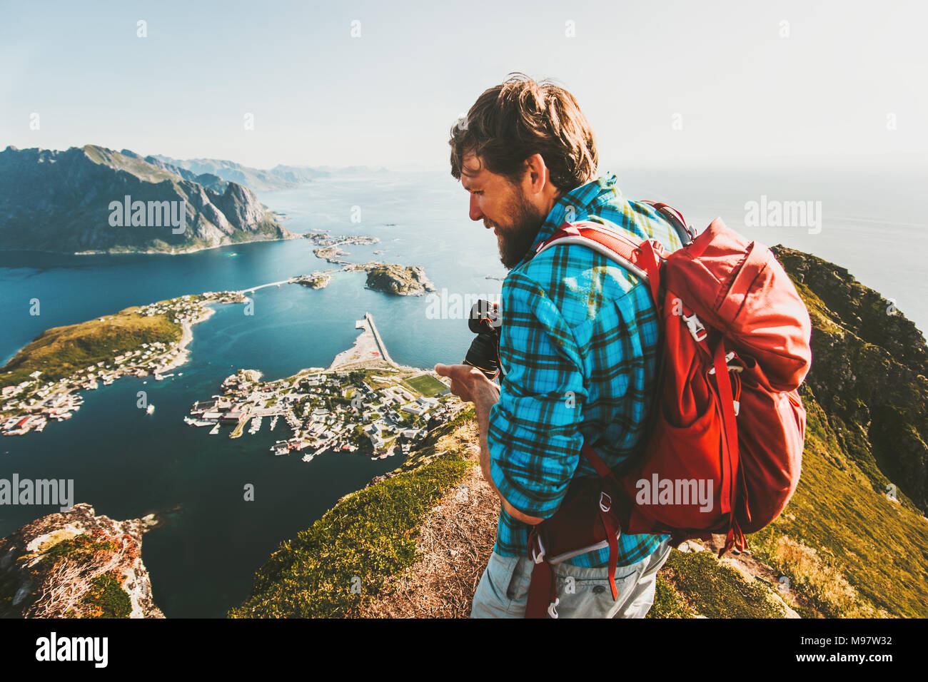 Man traveler with backpack and photo camera sightseeing view from  Reinebringen mountain in Norway lifestyle adventure traveling outdoor summer vacati - Stock Image