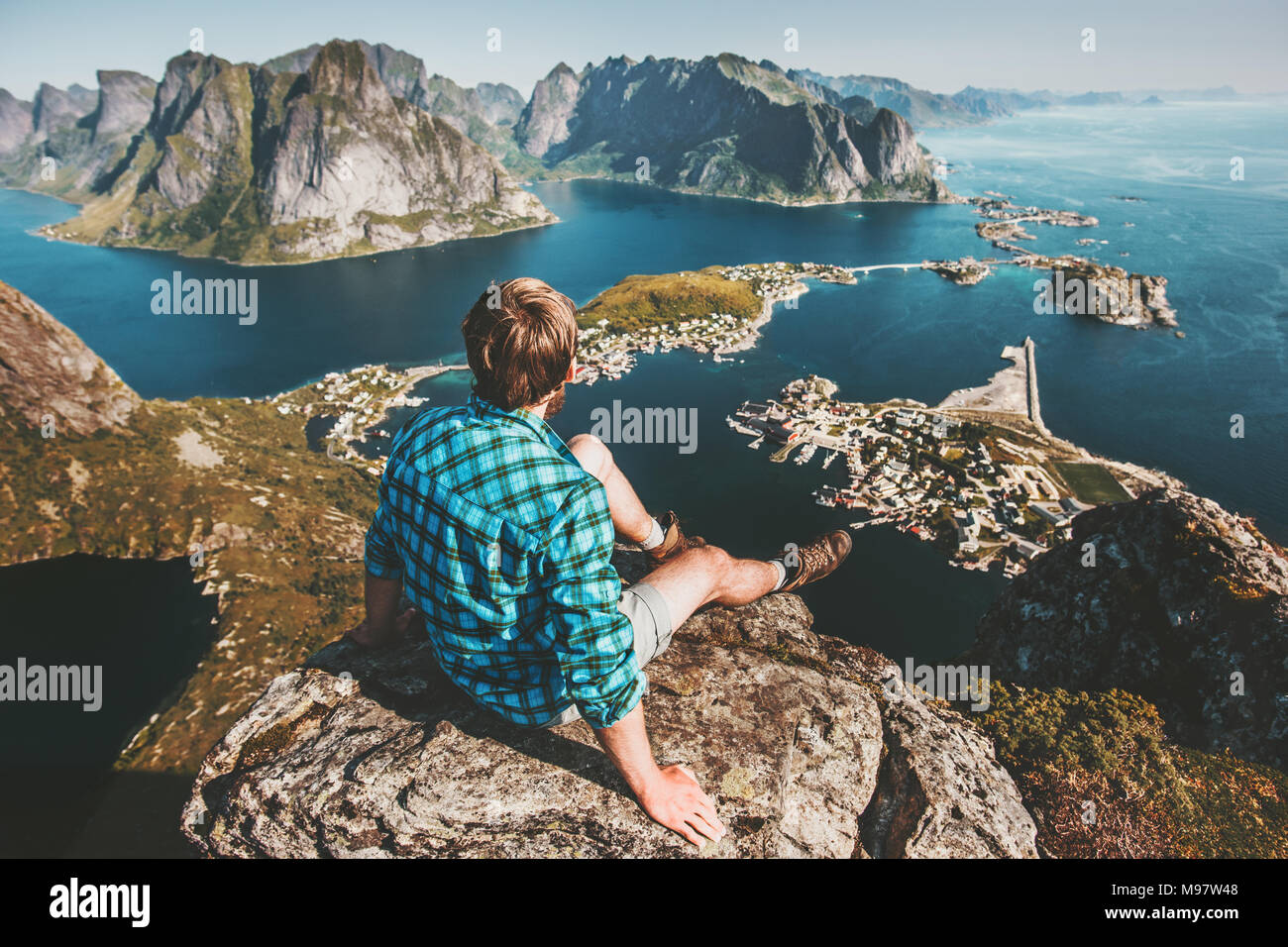 Man sitting on mountain top cliff above sea and rocks lifestyle travel adventure outdoor summer vacations tourist enjoying aerial view in Norway Lofot Stock Photo