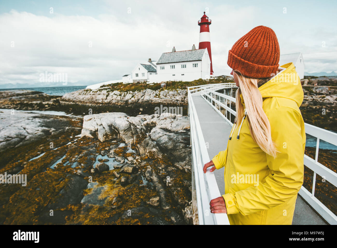 Woman sightseeing Norway lighthouse landscape Travel Lifestyle concept adventure tourist at vacations outdoor girl wearing yellow raincoat standing al - Stock Image