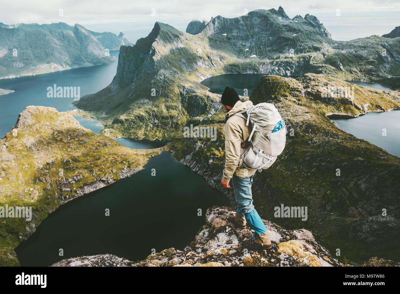 Discoverer man standing on cliff mountain in Norway Traveling lifestyle adventure concept hiking active summer vacations outdoor aerial view - Stock Image