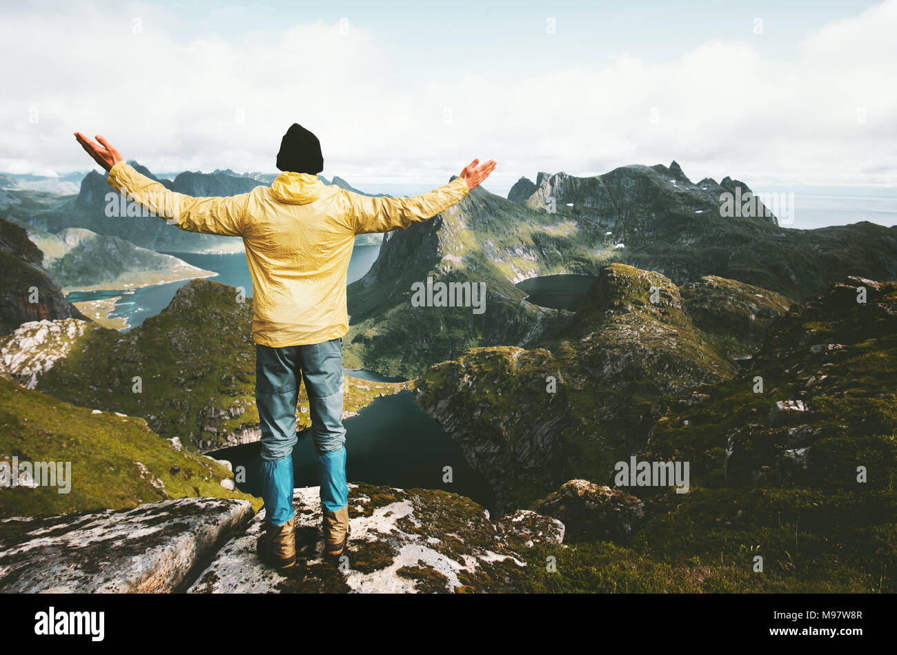 Traveler man happy raised hands on the mountain top in Norway wanderlust traveling explorer healthy lifestyle adventure concept active summer vacation - Stock Image