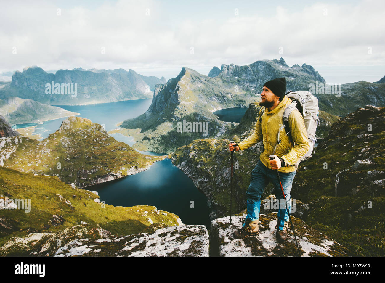 Bearded man traveler standing on cliff mountain in Norway Traveling with backpack healthy lifestyle adventure concept hiking active summer vacations o Stock Photo