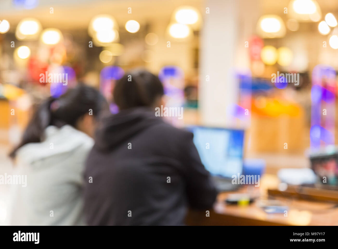 Blurred, out of focus, image of two people working on their computer in a brightly lit public place, good for any theme background - Stock Image