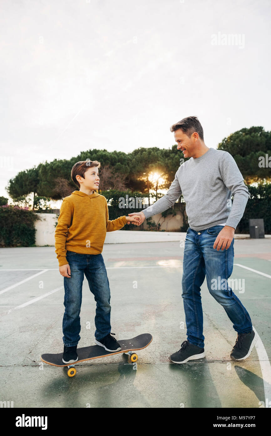 Father assisting son riding skateboard - Stock Image
