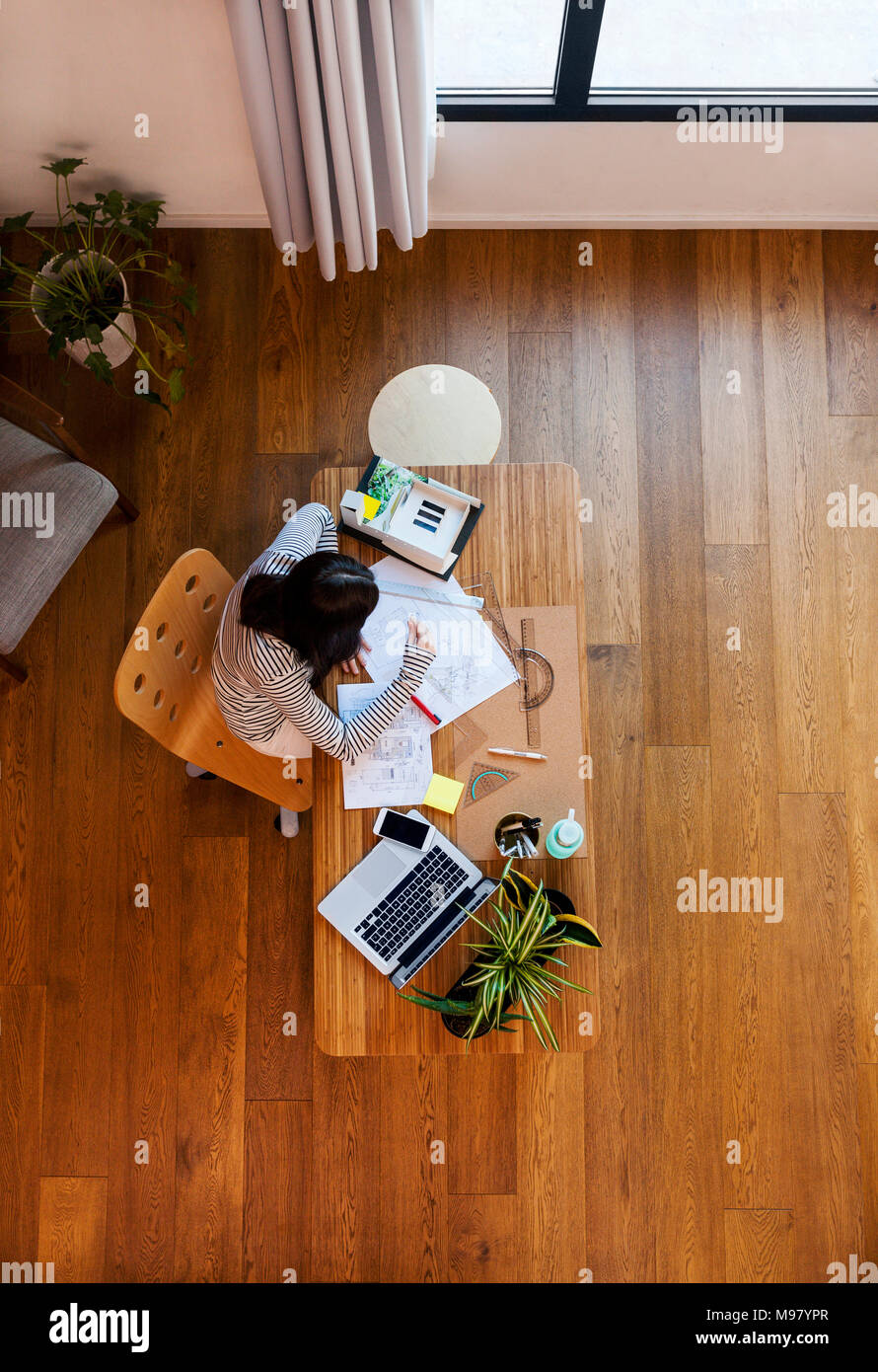 Young architect working in office, from directly above - Stock Image