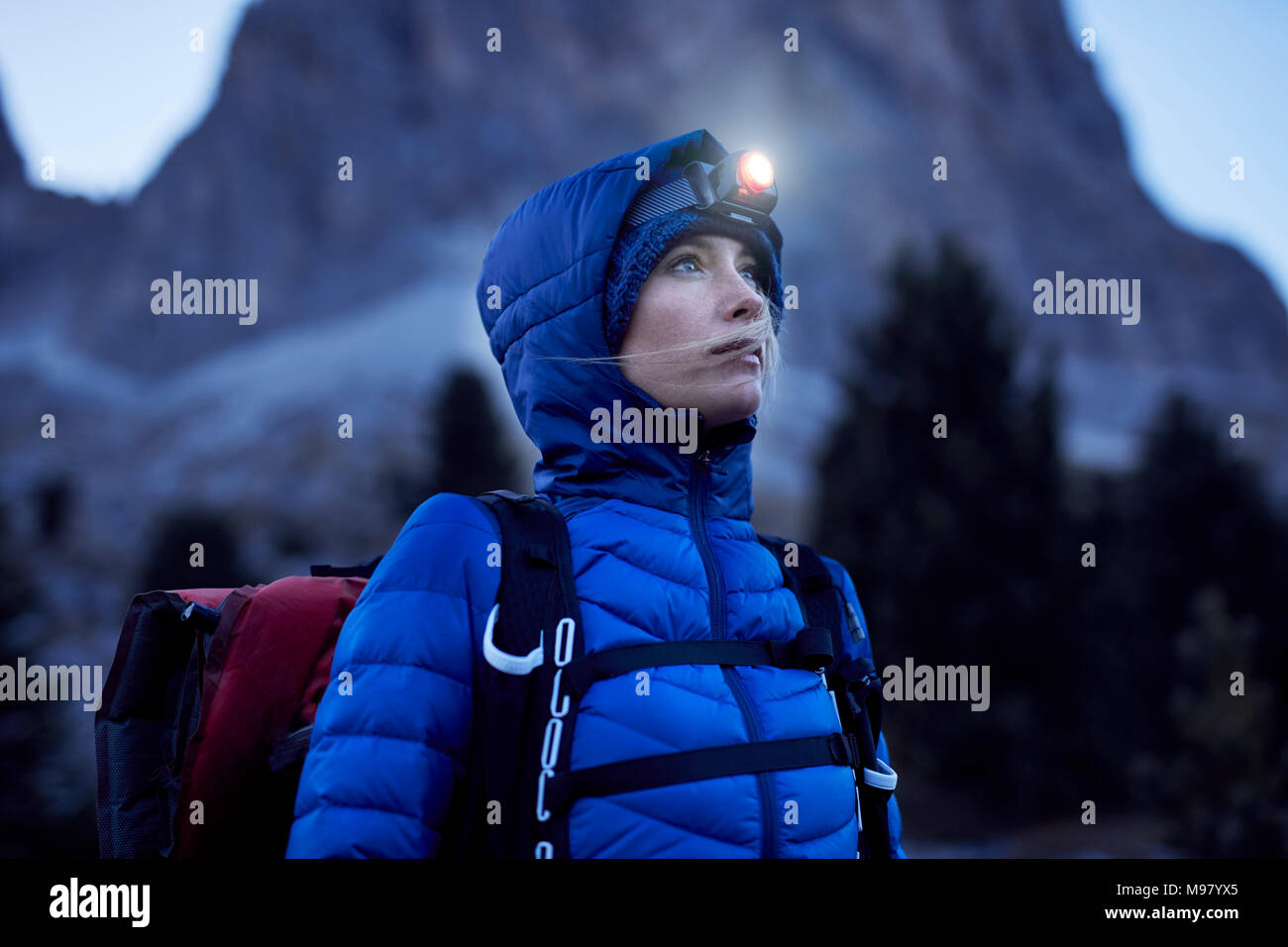 Young woman wearing headlamp at dusk in the mountains - Stock Image