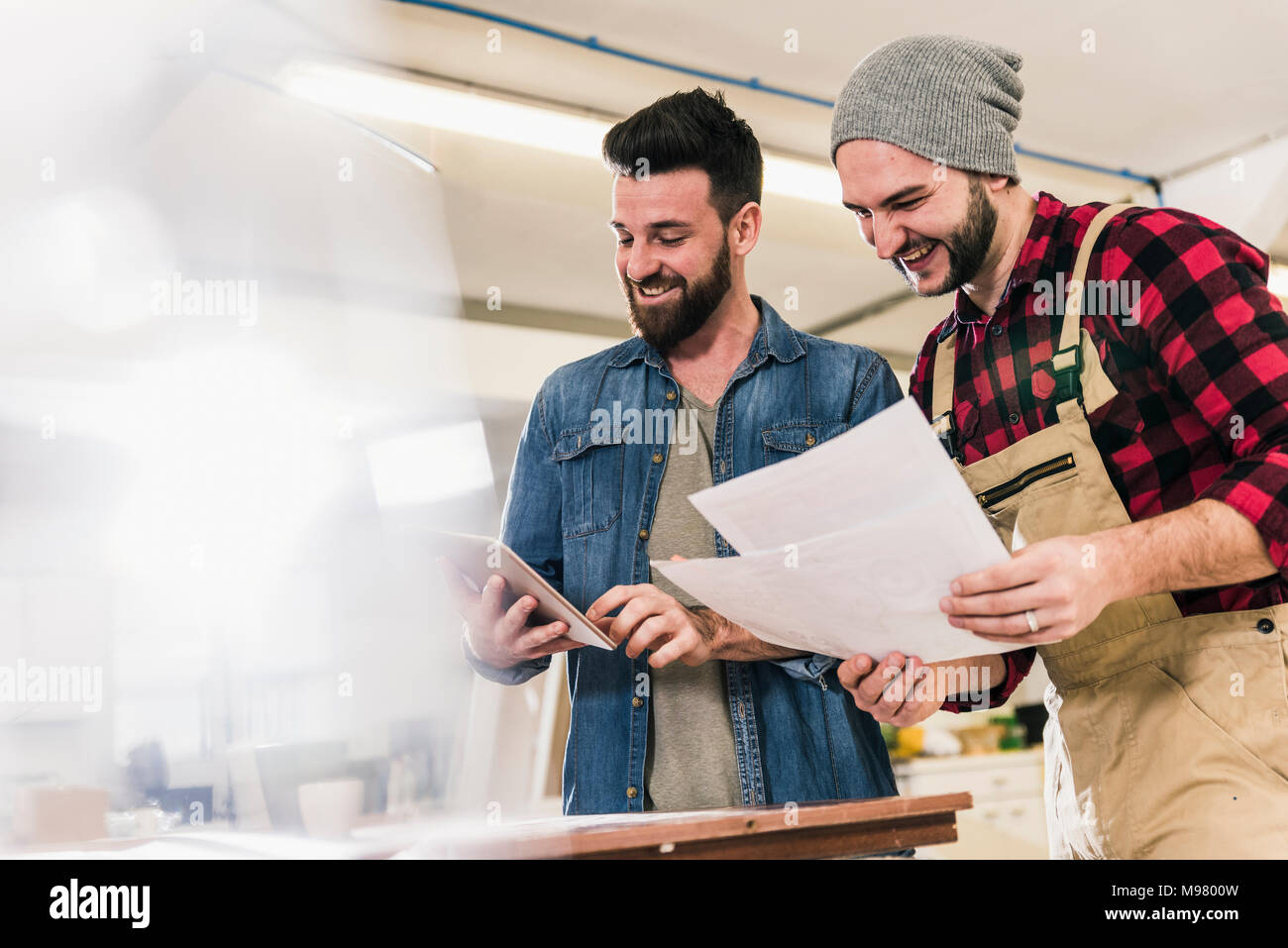 Two happy men with tablet looking at draft in workshop - Stock Image